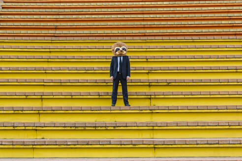 Businessman in black suit with meerkat mask standing on stairs - XLGF00031