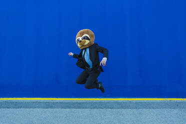 Businessman in black suit with meerkat mask jumping in the air in front of blue wall - XLGF00037