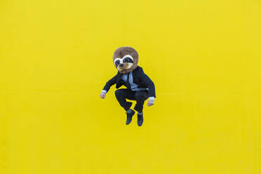 Businessman in black suit with meerkat mask jumping in the air in front of yellow wall - XLGF00046