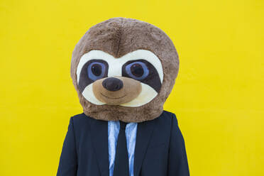Portrait of businessman with meerkat mask in front of yellow wall - XLGF00049