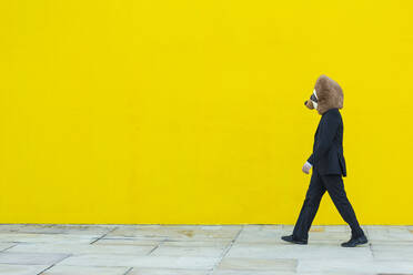 Businessman in black suit with meerkat mask walking in front of yellow wall - XLGF00055