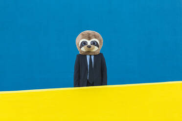 Portrait of businessman with meerkat mask standing behind yellow wall in front of blue background - XLGF00058