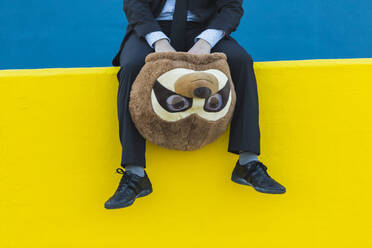Crop view of businessman in black suit sitting on yellow wall holding with meerkat mask - XLGF00061