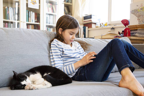Girl sitting on couch using digital tablet - LVF08822