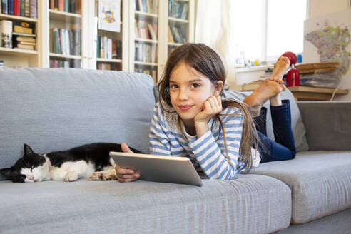 Portrait of smiling girl lying on couch with cat and digital tablet - LVF08825