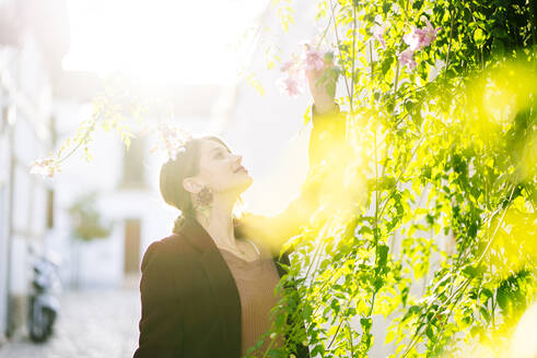 Smiling woman with a blossom in a scenic alley in the city - DGOF00828