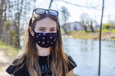 Girl with homemade protective mask at riverside - SARF04535