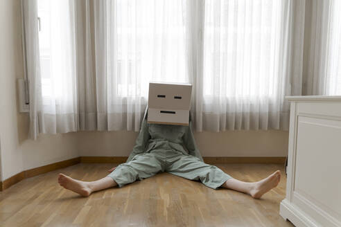 Woman wearing a cardbox on head with bored smiley sitting on the floor - AFVF06052