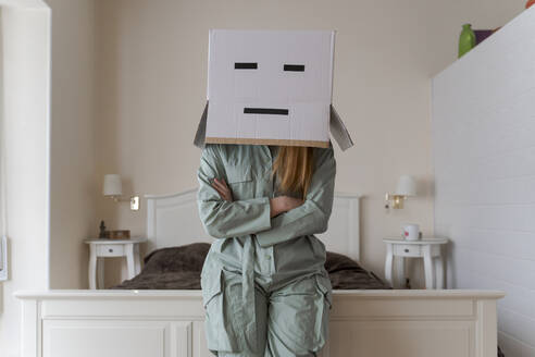 Woman wearing a cardbox on head with bored smiley leaning on bed at home - AFVF06067