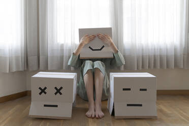 Woman wearing a cardbox on head with bored smiley sitting on floor in front of laptop, covering the eyes - AFVF06076