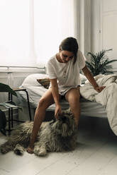 Mature woman standing up in the morning stroking her dog - ERRF03472