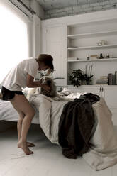 Mature woman cuddling her dog in the morning - ERRF03487