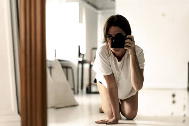 Mirror image of mature woman kneeling on floor taking photo with camera - ERRF03490