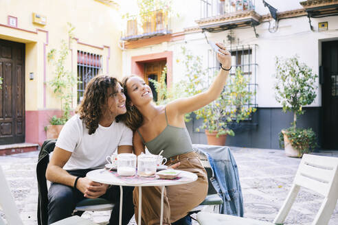 Young woman taking selfie through mobile phone with boyfriend while sitting at sidewalk cafe, Santa Cruz, Seville, Spain - DGOF00856