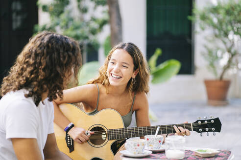 Happy young woman playing guitar while sitting with boyfriend at sidewalk cafe, Santa Cruz, Seville, Spain - DGOF00859