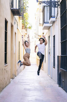 Full length of carefree couple jumping on narrow street during vacation at Santa Cruz, Seville, Spain - DGOF00880