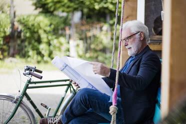 Senior man sitting outdoors looking at construction plan - JOSEF00258