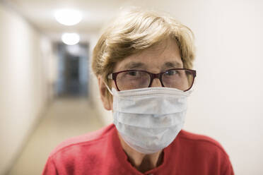 Senior woman with protective mask in corridor of retirement home - JATF01180