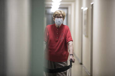 Senior woman wearing mask and walking with wheeled walker in corridor of retirement home - JATF01183