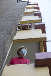 Senior woman wearing mask on balcony, retirement home - JATF01189