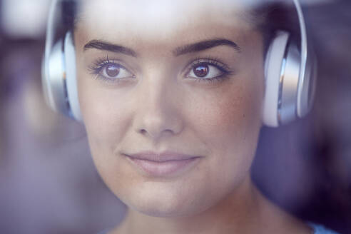 Portrait of young woman listening music with headphones looking out of window - JHAF00117