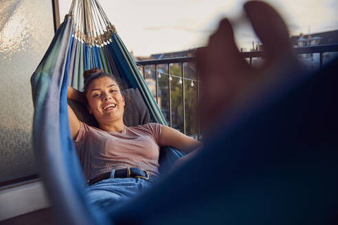 Portrait of happy young woman relaxing on hammock on balcony - JHAF00123