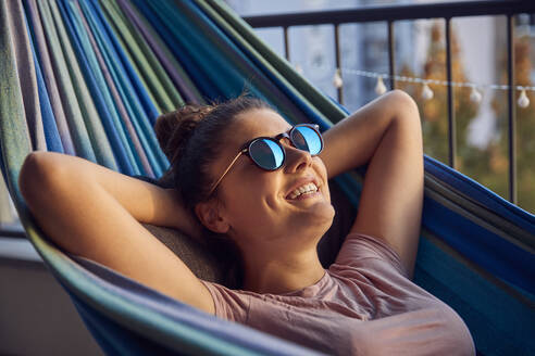 Portrait of happy young woman with sunglasses lying on hammock on balcony - JHAF00126