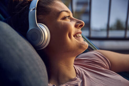 Happy young woman lying on hammock on balcony listening music with headphones - JHAF00129