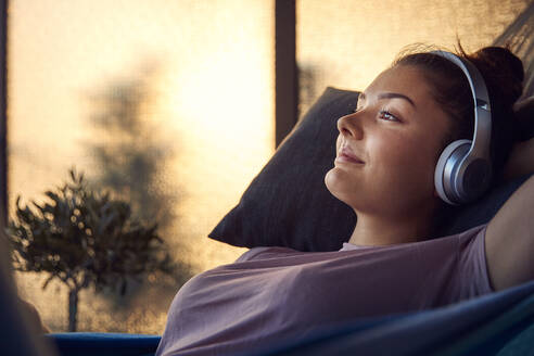 Smiling young woman lying on hammock on balcony listening music with headphones - JHAF00132