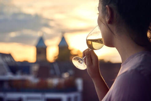 Young woman on balcony drinking glass of white wine at sunset - JHAF00138