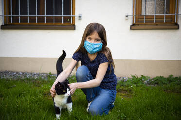 Girl wearing protective mask and stroking her cat in garden - LVF08828