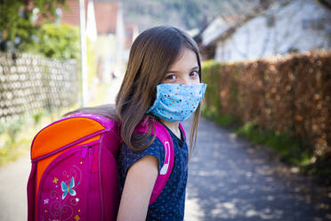 Girl with homemade protective mask on her way to school - LVF08831