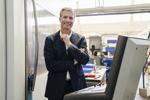 Mature businessman standing in production floor of factory - DIGF09791