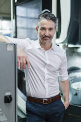 Mature businessman standing in production floor of factory - DIGF09830