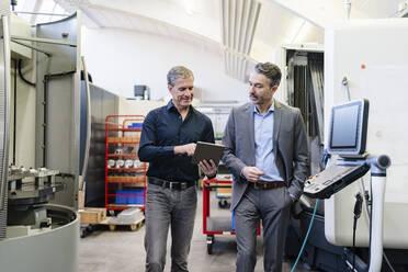 Businessmen in factory, having a meeting, using digital tablet - DIGF09836