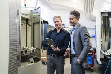 Businessmen in factory, having a meeting, using digital tablet - DIGF09839