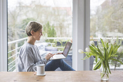 Mature woman working from home, using laptop, sitting on bench - ASCF01247
