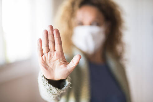 Woman with face mask showing palm of her hand, saying stop - SIPF02159