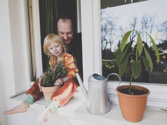 Father with daughter sitting on windowsill by potted plant - IHF00332