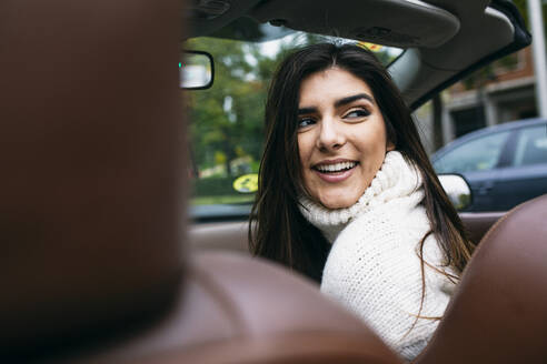 Smiling young woman looking over shoulder while traveling in car - ABZF03094