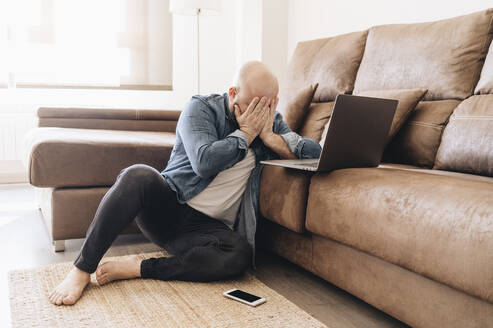Tired businessman with laptop covering face while sitting in living room at home - DGOF00901