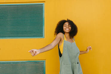 Portrait of happy young woman wearing overalls in front of yellow wall - TCEF00475