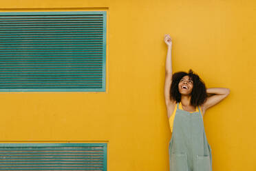 Portrait of happy young woman wearing overalls in front of yellow wall - TCEF00478