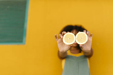 Close-up of young woman holding halved lemons - TCEF00481