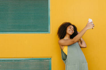 Portrait of happy young woman wearing overalls in front of yellow wall taking a selfie - TCEF00484