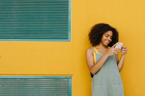 Smiling young woman wearing overalls in front of yellow wall using smartphone - TCEF00487