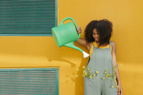 Young woman wearing overalls with watering can and yellow flowers in pockets - TCEF00490