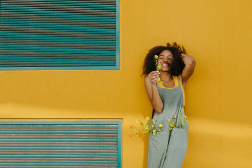 Portrait of happy young woman wearing overalls holding flowers in front of yellow wall - TCEF00493