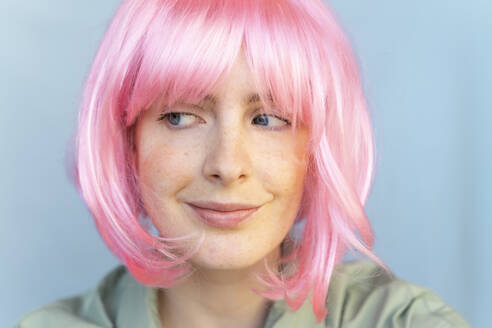 Portrait of young woman wearing pink wig glancing sideways - AFVF06090