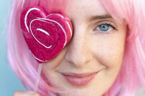 Portrait of young woman wearing pink wigwith heart-shaped lolly covering her eye - AFVF06093